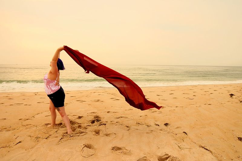 Woman holding red material blowing in the wind Calm Meditation Tranquility Peace Freedom Red EyeEm Selects Beach Sea Land Water Sky Horizon Over Water Real People One Person Leisure Activity Horizon Sand Lifestyles Beauty In Nature Women Full Length Sunset Scenics - Nature Nature Outdoors Human Arm