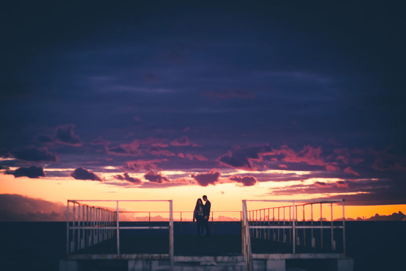 Silhouette people standing on railing against sky during sunset