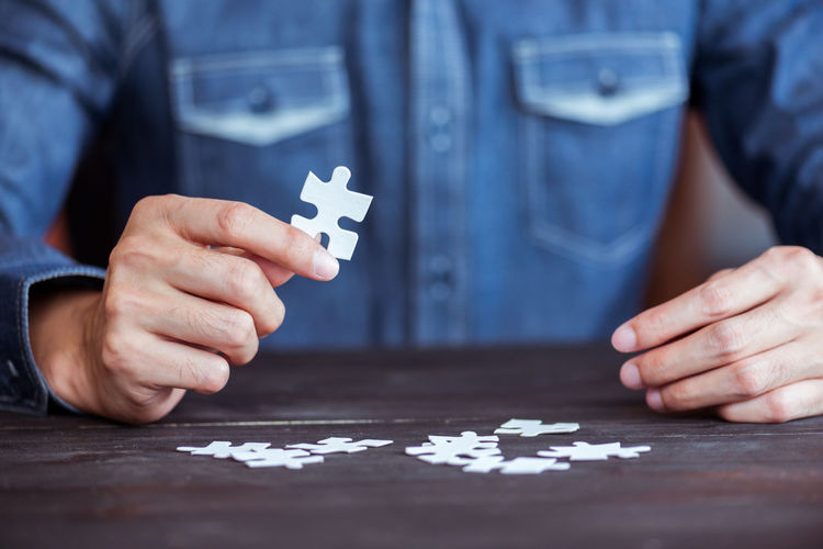 Midsection Of Person Holding Jigsaw Puzzle