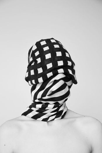 Portrait of shirtless man covering face against white background