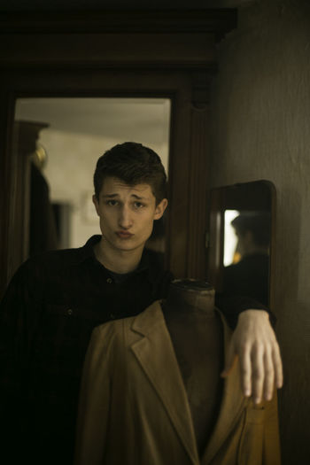 Portrait of young man puckering while leaning on mannequin with blazer at home