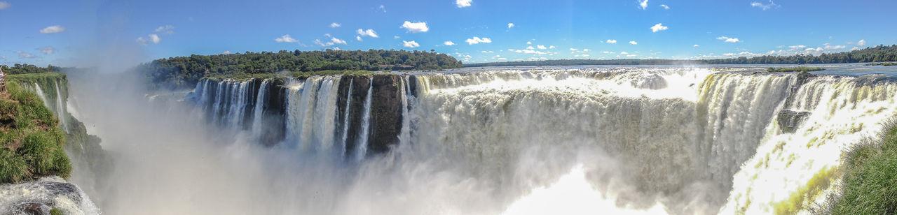 Panoramic view of iguazu falls against sky
