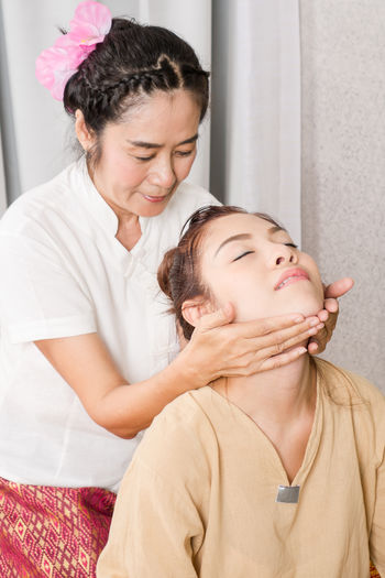 Woman giving massage to customer at spa