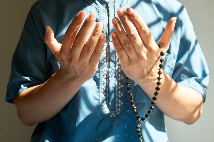 Muslim man praying with rosary on hand palm