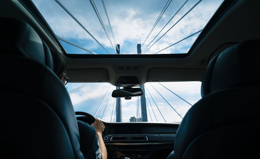 Low angle view of sky seen through car windshield