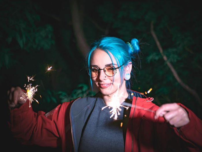 Close-Up Of Young Woman Burning Sparklers At Night