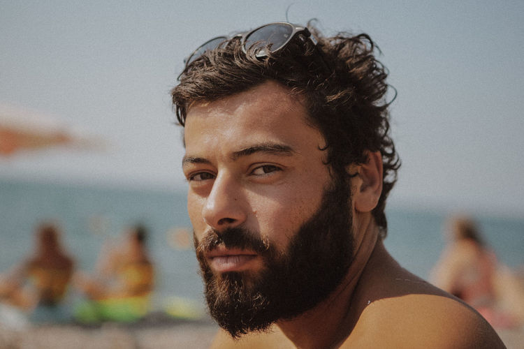 Beach Beard Beautiful People Close-up Contemplation Facial Hair Focus On Foreground Hairstyle Headshot Leisure Activity Lifestyles Looking Looking At Camera One Person Outdoors Portrait Real People Sea Young Adult Young Men