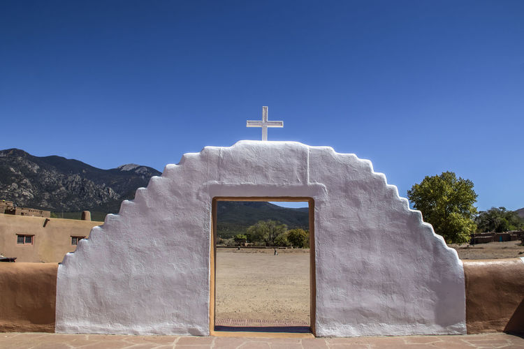 White painted mud adobe gate with cross on top looking out of a mission courtyard onto mountains and trees and a pueblo resident carrying a bucket with other buildings in background Gate Pueblo Church Mission Mud Adobe Whitewashed White Paint Mountains Framed Architecture Sky Cross Culture Historic Taos Landmark Religion Travel Village Door Indian Traditional History Tourism Catholic Unesco American USA Entrance Heritage Native Ancient Tribal Southwest  Famous Stucco New Mexico Pre-Hispanic Sightseeing Christianity Indigenous  Destination Tourist Historical Abode Attraction Taos Pueblo