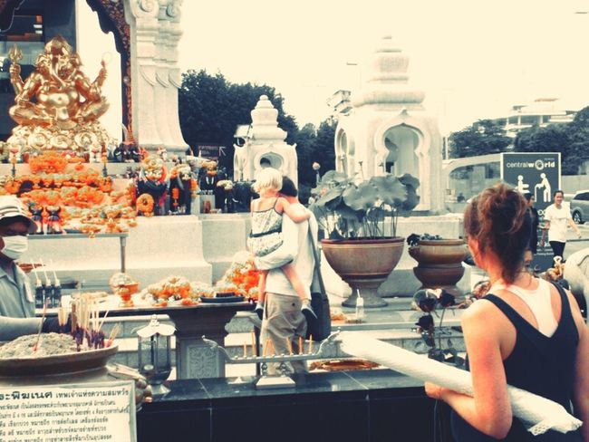 An american family places flowers at a statue of Lord Ganesha