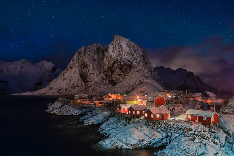 Illuminated stilt houses by lake and mountains during winter at night