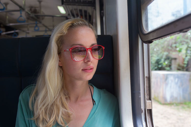 Close-up of woman wearing eyeglasses sitting in train