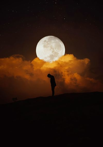 Silhouette person standing against moon at sunset