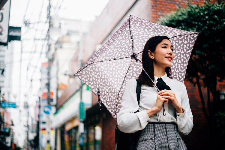 Young woman looking away while standing in rain