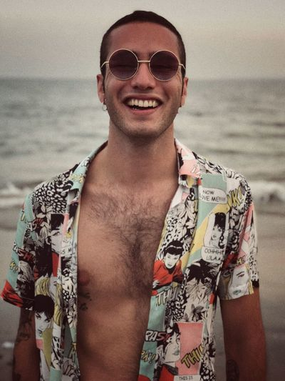 Portrait Of Happy Young Man Wearing Sunglasses At Beach