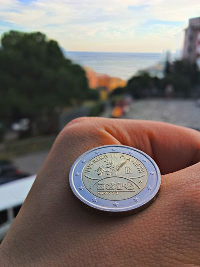 Close-up of coin on hand with sea in background
