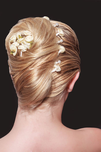 View from the back of a woman with an elegant blond hairstyle with her long hair swept up into a bun and secured with a hair ornament Back Hair Sophisticated Accessories Black Background Blond Hair Close-up Flower Glamourous Hair Fashion Hairstyle Headshot Indoors  Juwelry Maintained Neck Node People Rear Rolê Studio Shot Style Wedding Hair Wedding Hairstyles Women