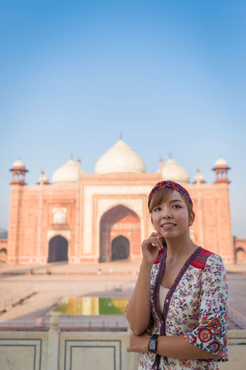 Woman looking away while standing against taj mahal