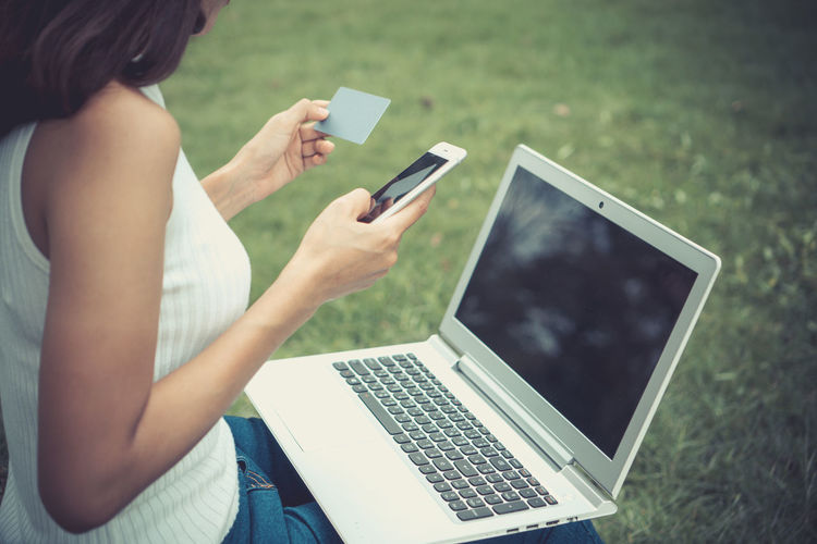 Midsection Of Mid Adult Woman Doing Online Shopping While Sitting On Grassy Field