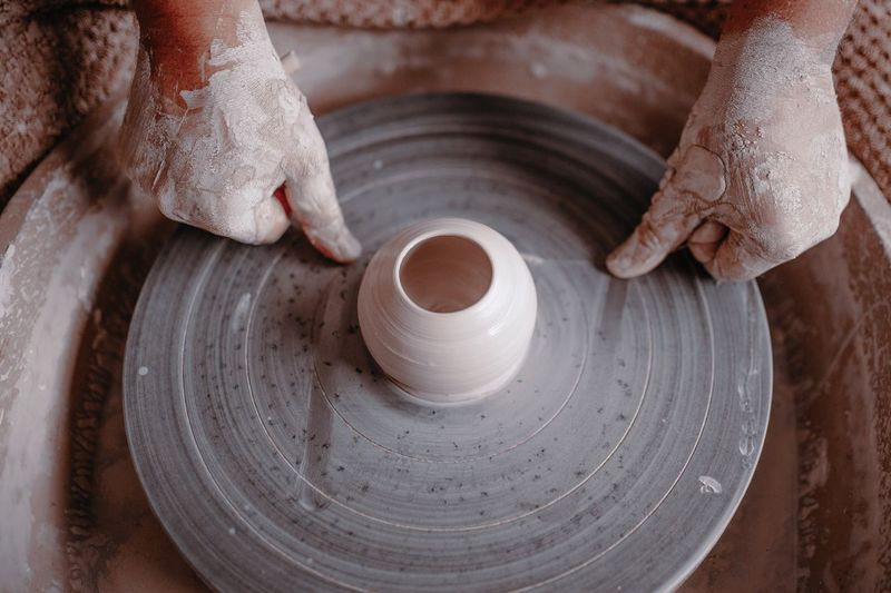 Muddy Hands Of Potter On Spinning Wheel At Workshop