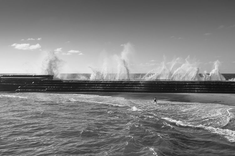 This picture was captured in Bajamar in Tenerife in 2015. We can observe a young boy being suprised by raging waves which tried to tear some of the town's breakwaters. Bajamar, Tenerife The Traveler - 2018 EyeEm Awards Black And White Photography Digital Photography People Photography Tenerife Island Water Waves, Ocean, Nature