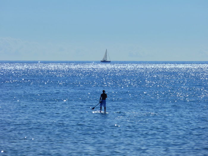 Full length rear view of shirtless man paddleboarding on sea during sunny day