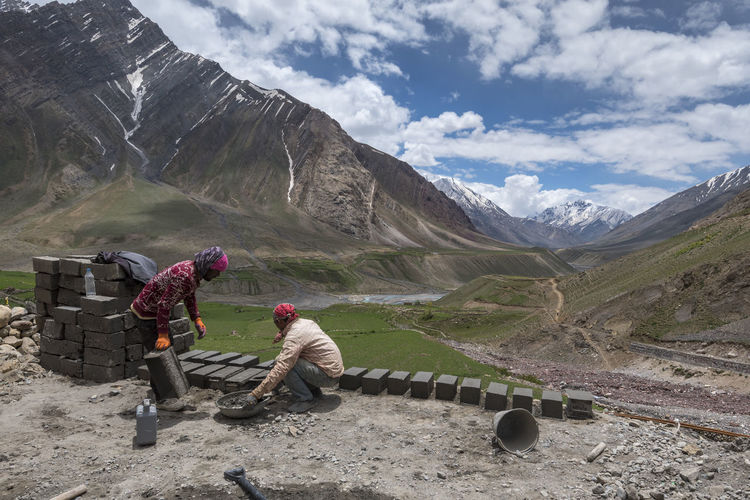 People working on mountain against sky