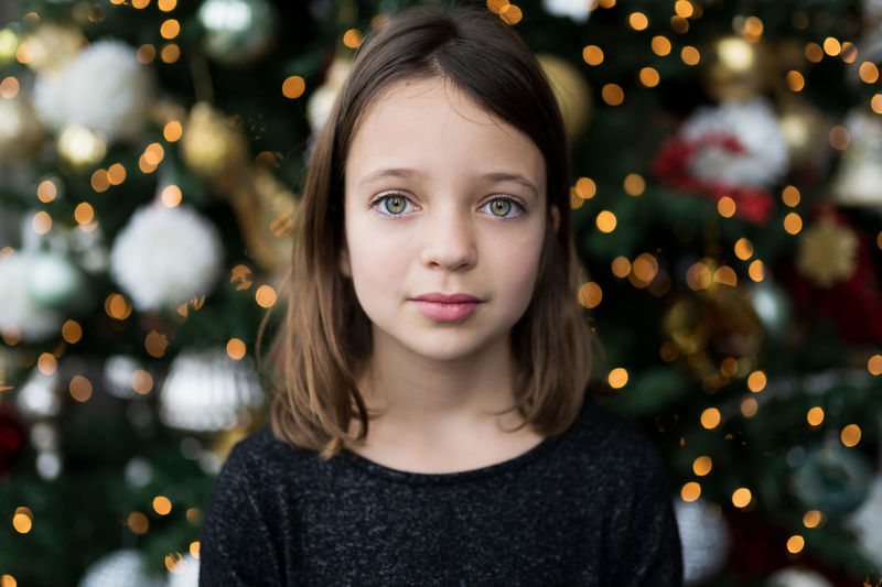 Portrait of girl against christmas tree
