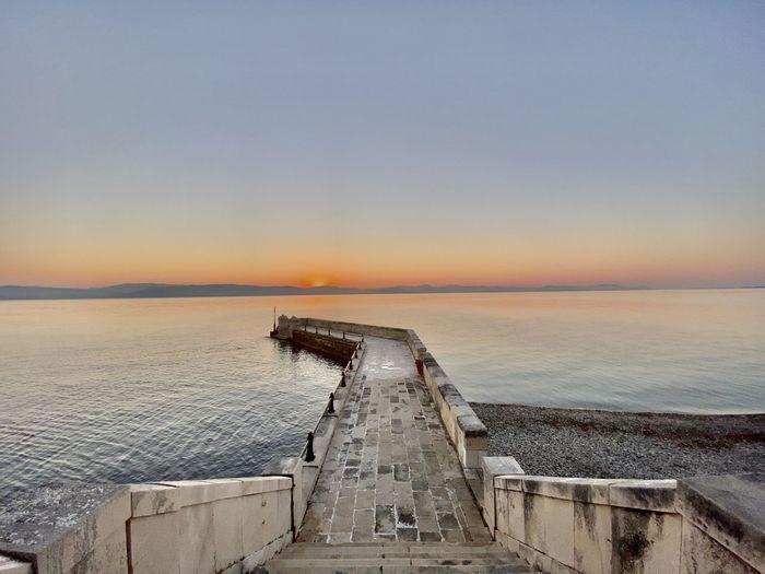 Pier in sea against sky