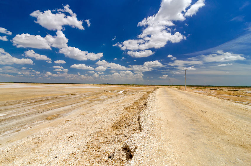 Dirt road passing through desert flatlands in La Guajira, Colombia Beautiful Blue Cabo Cabo De La Vela Caribbean Coast Colombia Desert Holiday La Guajira La Guajira Colombia Landscape Ocean Outdoors Relax Sand Scenic Sea Sky Sunset Tourism Travel Tropical Vacation Water