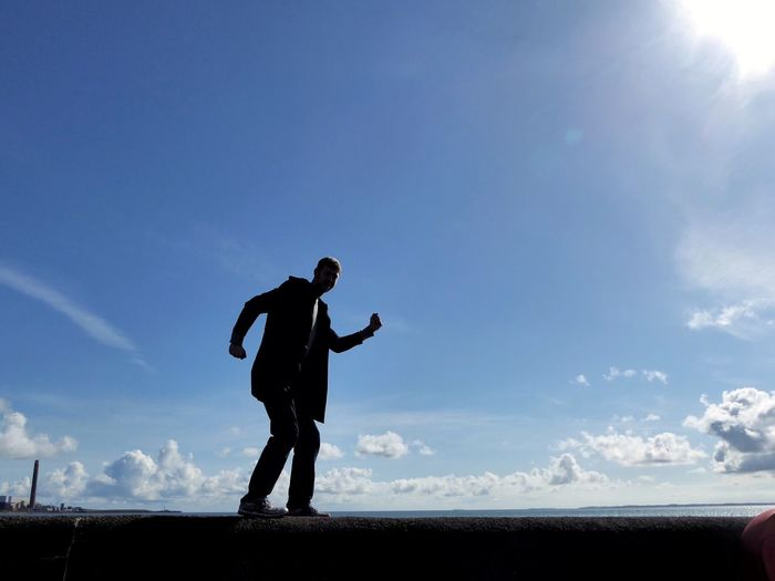 Sky One Person Real People Men Full Length Outdoors Man On Wall Dancing Walking Walking On Sunshine Happy Lifestyles Shadow Blue Sky Cloud - Sky Northern Ireland Wall Sea Sea And Sky Leisure Activity Standing Silhouette One Man Only EyeEmNewHere