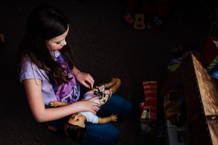 Girl Playing Doll At Home