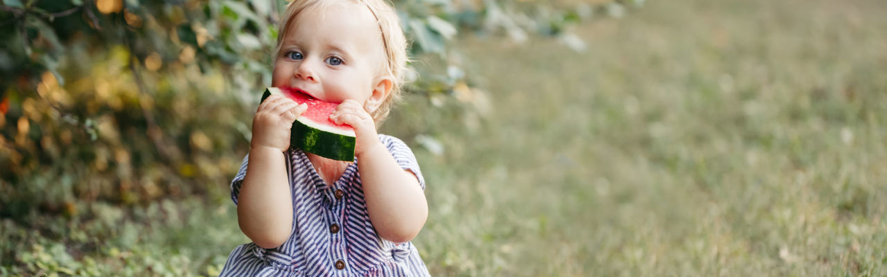 Portrait of cute girl eating watermelon outdoors