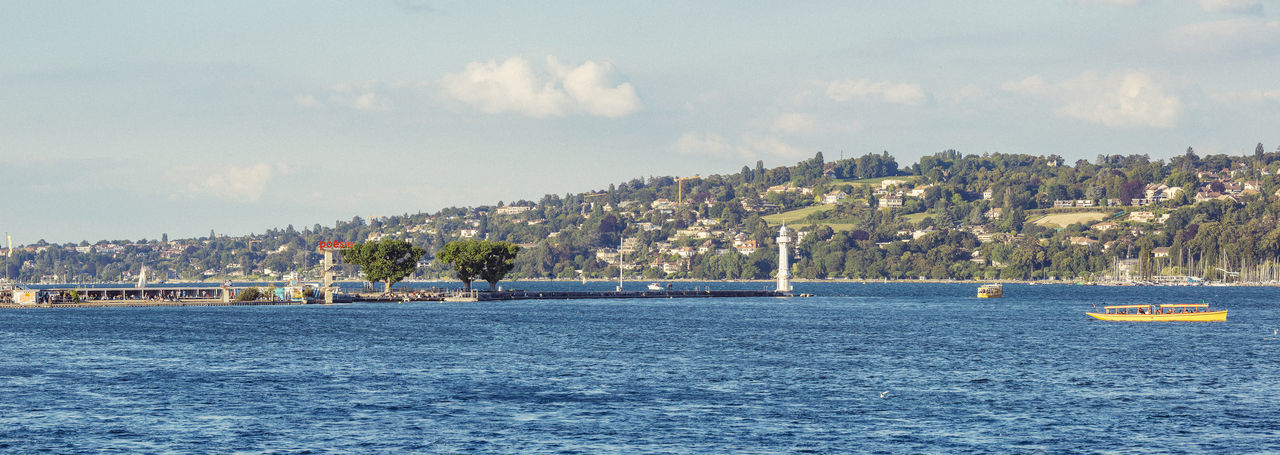 Panoramic view of the Bains des Paquis pier and lighthouse. Architecture Bains Des Paquis Boat Building Exterior Built Structure City Day Geneva Jetty Lake Lake Geneva Nature Nautical Vessel No People Outdoors Panoramic Pâquis Sky Switzerland Transportation Water Waterfront