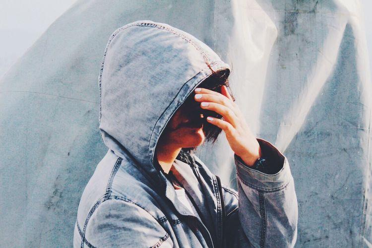 Man wearing denim hood while shielding eyes against canvas