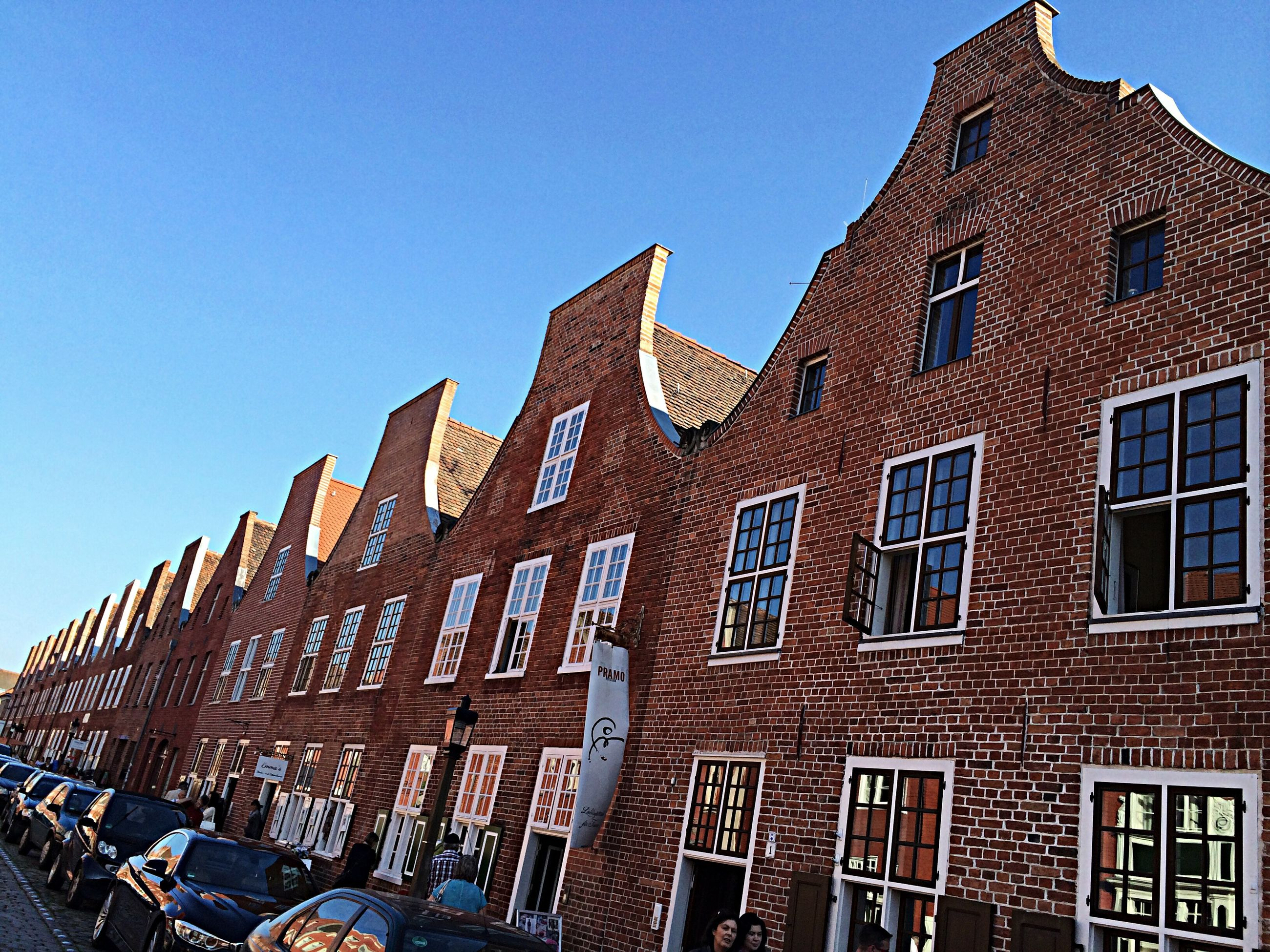 building exterior, architecture, built structure, clear sky, low angle view, window, building, city, blue, day, sunlight, residential building, outdoors, residential structure, tower, no people, facade, sky, copy space, history