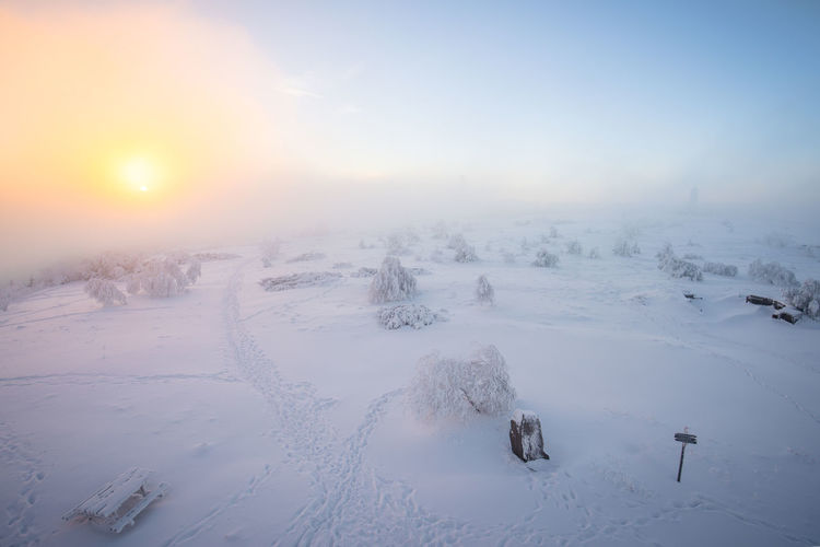 Scenic view of frozen landscape against sky during winter
