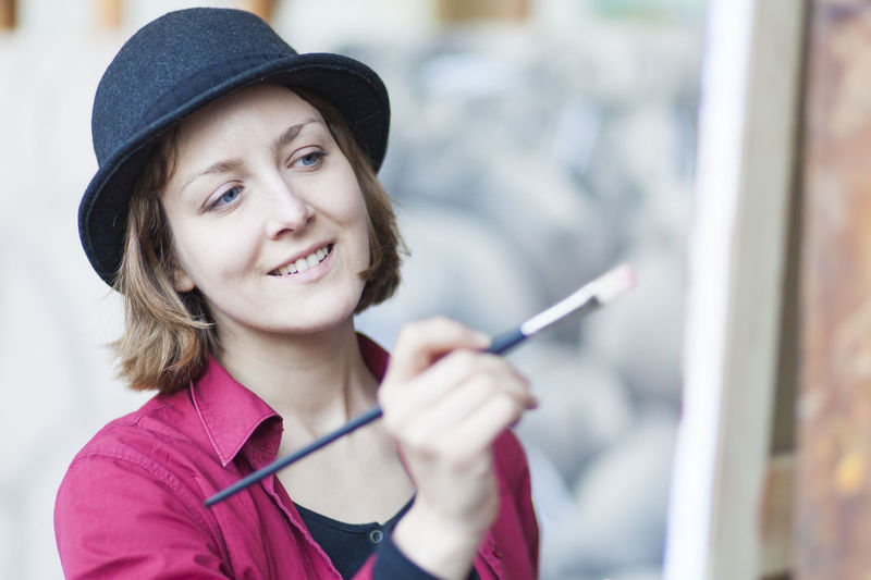 Smiling woman holding brush while painting on canvas