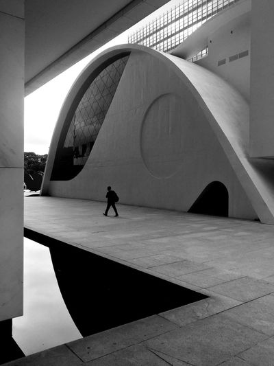 Loneliness The Architect - 2019 EyeEm Awards Architecture Built Structure Real People One Person Day Building Exterior The Minimalist - 2019 EyeEm Awards Lifestyles Footpath Travel Destinations City Nature Walking Sunlight Outdoors Water Shadow Men Leisure Activity Incidental People