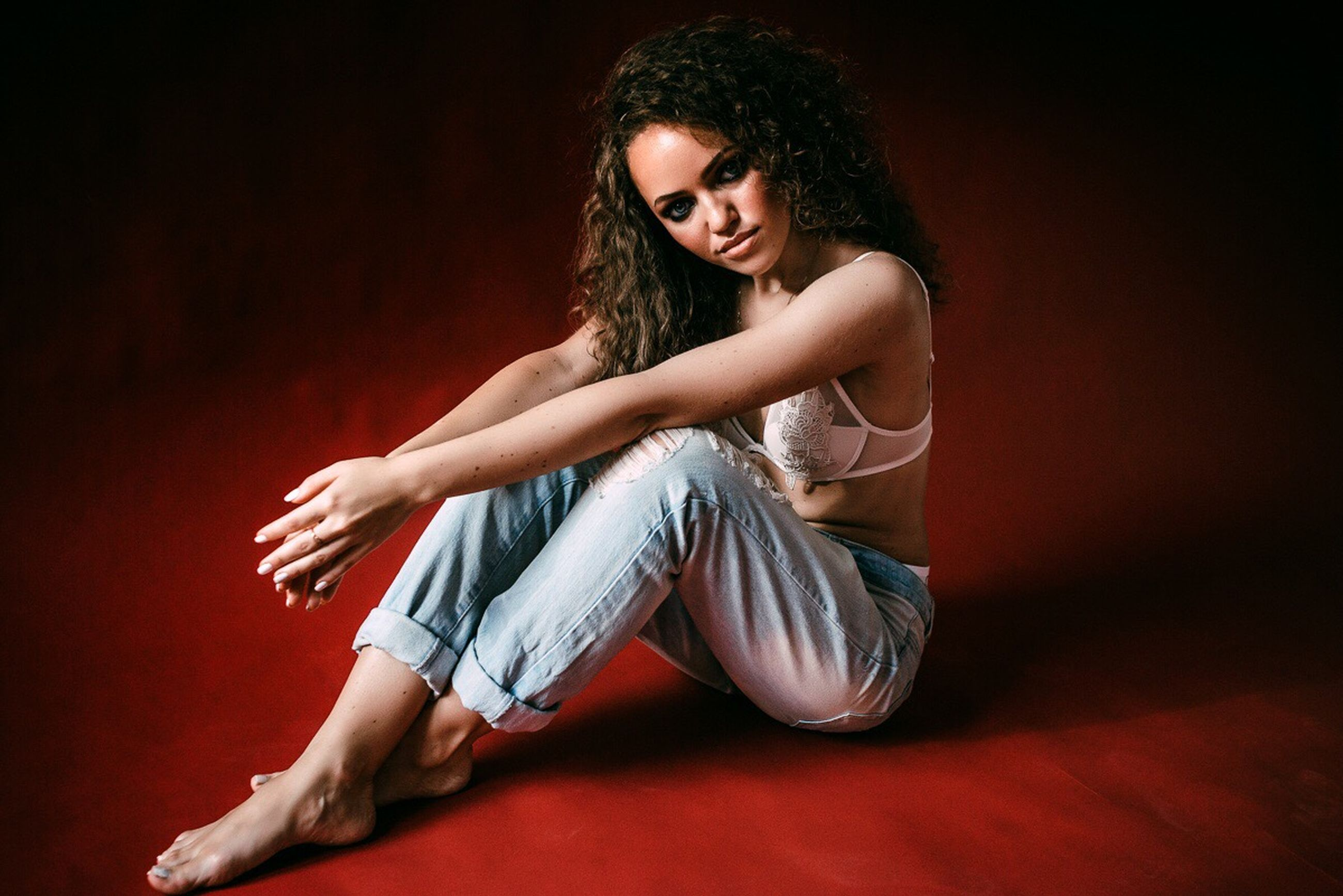 young adult, studio shot, young women, full length, one person, real people, sitting, beautiful woman, casual clothing, leisure activity, portrait, looking at camera, curly hair, lifestyles, beauty, fashion model, indoors, day