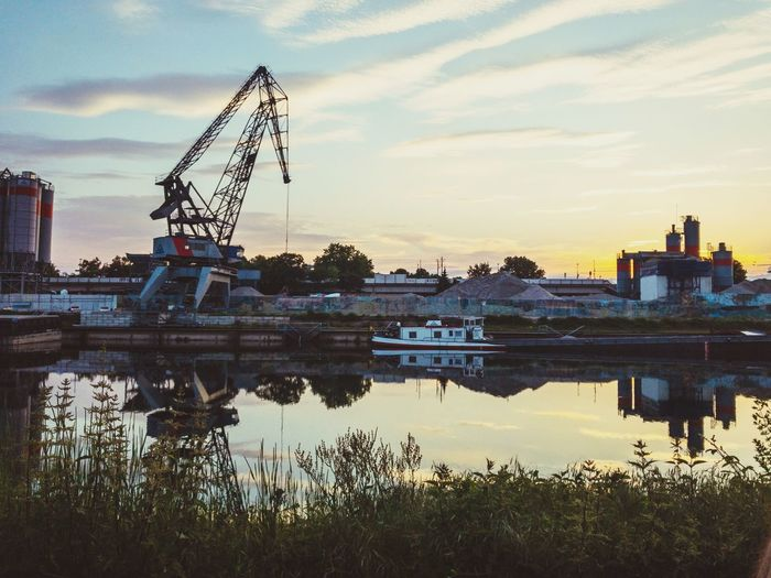 Cranes at riverbank against sky during sunset
