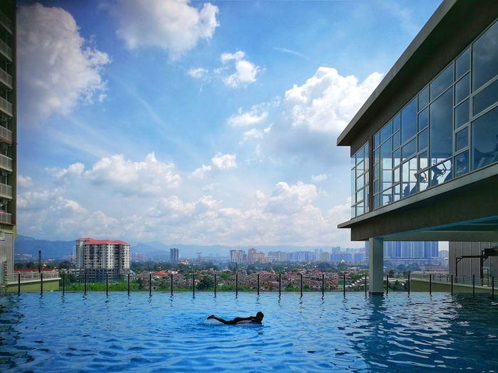 A boy swimming in the pool Boy Swim City Water Cityscape Nautical Vessel Urban Skyline Skyscraper Sky Architecture Building Exterior
