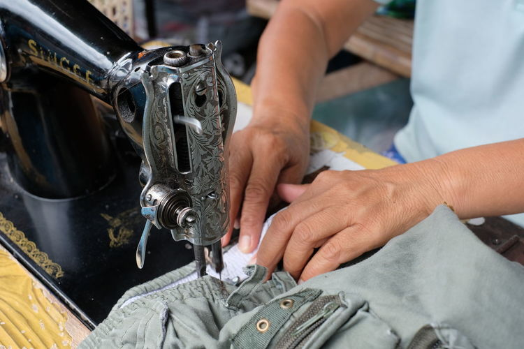 Midsection of person sewing textile on machine