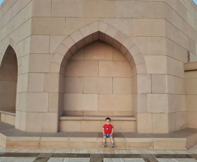 Full length of baby boy sitting outside mosque
