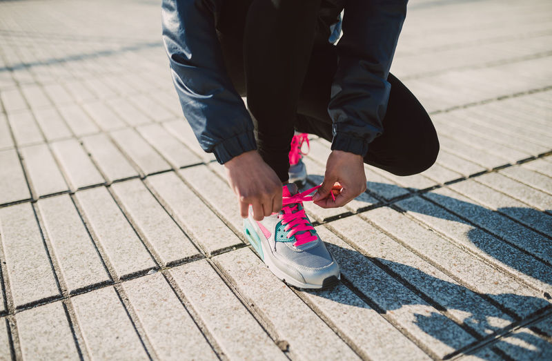 Low section of person tying shoelace while crouching on footpath