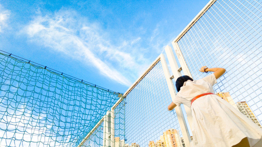 Low angle view of girl standing by fence at schoolyard against sky