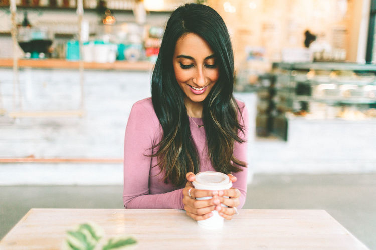 A young Indian woman holding a cup of coffee. Smiling Young Adult One Person Happiness Long Hair Food And Drink Coffee Young Women Beauty Cafe Beautiful Woman