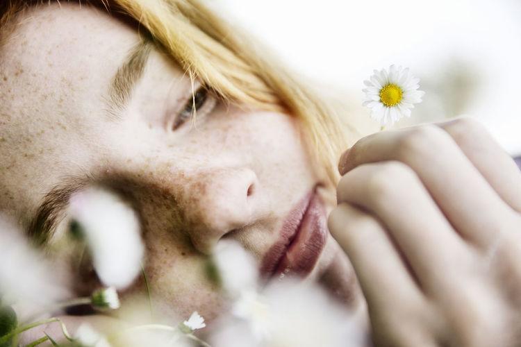 Close-up portrait of beautiful woman against white flowering plants