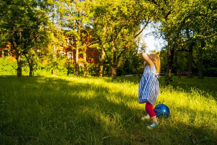 Full Length Of Girl Playing With Ball On Grass Field