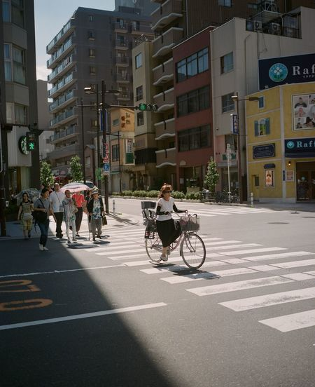 City Building Exterior Architecture Transportation Street Built Structure Group Of People Road Marking Mode Of Transportation Road Real People City Life Symbol Bicycle Building Land Vehicle Marking Crossing City Street Men Outdoors Riding Office Building Exterior The Street Photographer - 2019 EyeEm Awards