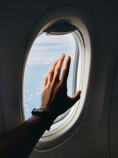 Cropped hand of man reaching airplane window